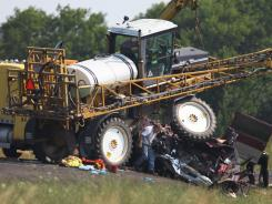 Officials work the scene of a crash where police say a car passing a slow-moving farm tractor on a curve sideswiped an oncoming van carrying 13 Amish farmers Tuesday.