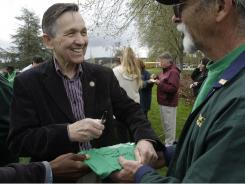 Rep. Dennis Kucinich, D-Ohio,  signs a T-shirt for Robert Delvin, a worker at Western State Hospital. He was in Lakewood, Wash.