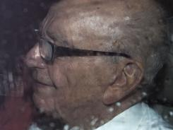 News Corp. chief Rupert Murdoch leaves the House of Parliament in London on Tuesday after giving evidence to a Parliamentary Select Committee on the phone hacking scandal and getting shaving cream in his face by a protester.