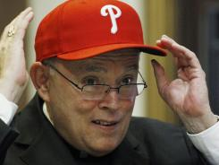 Denver Archbishop Charles Chaput puts on a Philadelphia Phillies hat Tuesday after the Vatican named him Cardinal Justin Rigali's successor as Archbishop of Philadelphia.