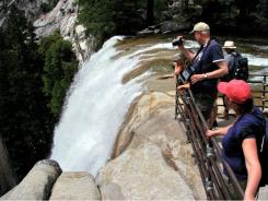 Visitors pause behind a safety railing at a Vernal Fall observation point last summer.