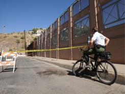 A bicycle-mounted Border Patrol agent monitors a section of the U.S.-Mexico border in Nogales, Ariz.