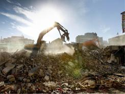 An excavator works on clearing rubble in downtown Christchurch, New Zealand, on July 8.