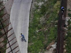 Two men illegally cross the border fence separating Nogales, Ariz., and Mexico in 2010.