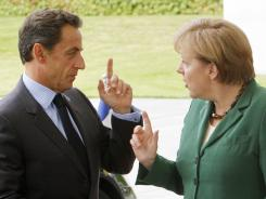 German Chancellor Angela Merkel, right, welcomes French President Nicolas Sarkozy in Berlin on Wednesday.