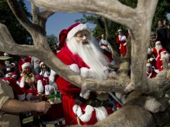 Santas visit reindeers at Copenhagen Zoo on Tuesday. About 120 Santas from all around the world arrived in Copenhagen to participate in the annual World Santa Claus Congress.