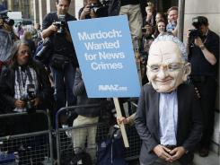 A protester wearing a Rupert Murdoch mask is photographed by media outside parliament in London on Tuesday.