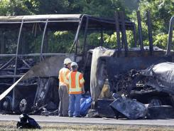 Workers evaluate the scene where a tractor-trailer crashed into a tour bus carrying 50 people on the New York State Thruway in Waterloo, N.Y.