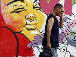 A man wipes his face as he passes a painted mural in Trenton, N.J. on Friday.