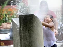 A child plays in a sprinkler Saturday in New York.  The National Weather Service said the temperature was 92 degrees in Central Park at 10 a.m. Saturday.