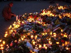 A Norwegian man lights a candle to pay tribute to victims of the twin attacks  in central Oslo, Norway, on Saturday.