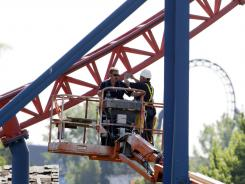 Workers inspect The Ride of Steel roller coaster at Darien Lake Theme Park Resort in Darien, N.Y., on July 9.