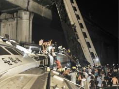 Emergency workers and people work to help passengers from the wreckage of train after two carriages from a high-speed train derailed and fell off a bridge in Wenzhou in east China's Zhejiang province.