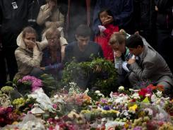 People pay tribute to victims of the twin attacks before a memorial service at Oslo Cathedral Sunday.
