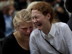 Women react at Oslo Cathedral after a service for the victims of Friday's bomb attack on Norway's government headquarters and shooting at a Labor Party island retreat.