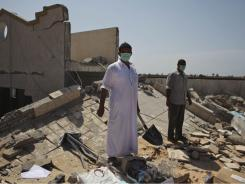 Libyan men stand on top of the remains of a medical clinic that was destroyed during a NATO airstrike early Monday morning near Tripoli.