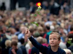 A boy holds up a rose as hundreds of thousands gather Monday at a memorial vigil following Friday's twin extremist attacks in Oslo, Norway.