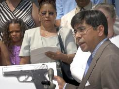 Attorney Hector Pineiro holds a photograph of a Kahr Arms' handgun during a news conference in Worcester, Mass.