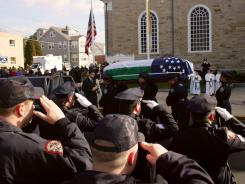 In this 2006 file photo, police salute the casket bearing the remains of James Zadroga, a former New York City police detective who worked hundreds of hours at World Trade Center following the September 11 terrorist attacks.