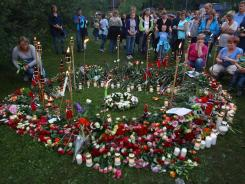 People lay flowers after Tuesday's vigil walk near Utoya Island in Sundvolden, Norway. Anders Behring Breivik has been detained in last week's massacre.