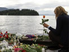 A woman holds a rose Tuesday in Sundvollen, close to Utoya island, where at least 68 people were killed.