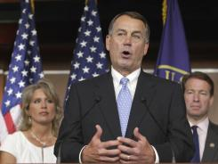 House Speaker John Boehner, flanked by Rep. Renee Ellmers and Rep. Peter Roskam, discusses the debt crisis showdown. His proposal would raise the debt limit and make spending cuts.