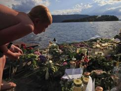 A youth looks at flowers and tributes Thursday left in Sundvollen, close to Utoya island, where gunman Anders Behring Breivik killed at least 68 people, near Oslo, Norway.