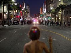 Noel Buller, 21,  from Los Angeles, stands in the middle of Hollywood Boulevard in Los Angeles holding up a peace sign while facing a line of Los Angeles Police on Wednesday.