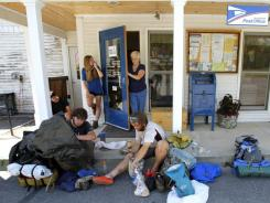 Local Norma Desrochiers makes her way out of the post office where Appalachian Trail thru-hikers Greg Brown, left, and David Hyman, both of Pleasantville, N.Y., sort through their gear, while Madelyn Hoagland-Hanson, of Philadelphia, speaks on the phone, outside the post office in Caratunk, Maine, on Thursday.