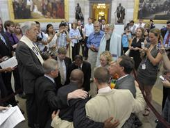 Civic and religious leaders pray inside the Capitol Rotunda on Capitol Hill in Washington, The group, who were protesting proposed budget cuts with debt ceiling negotiations, were arrested by Capitol Hill Police. 