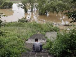 A man sits on the stairs at a flooded ecology park in Seoul, South Korea, on Friday.