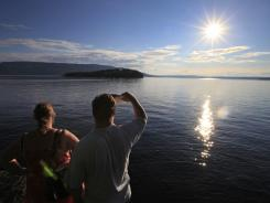 A couple watches the sun set on Friday in Sundvollen, close to Utoya island, background, where gunman Anders Behring Breivik killed more than 70 people.