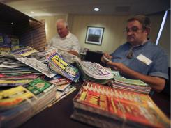 "John Flara, right, from New Cumberland, W.Va., and Walter Johnston, from Hull, Mass., sort through and trade lottery tickets during the ""Lottovention,"" in Northeast Philadelphia on Friday."