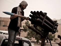A rebel fighter loads a rocket launcher during fighting in the village of Josh as fighting continues between rebel forces and those loyal to the Libyan leader on Sunday.