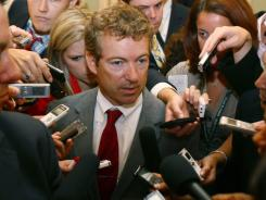 Sen. Rand Paul, R-Ky., co-founder of the Senate Tea Party Caucus, is surrounded by reporters at the Capitol on Monday.