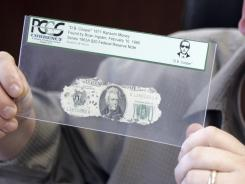 "Brian Ingram displays a $20 bill that ""D.B. Cooper"" was carrying when he parachuted with his ransom in 1971."