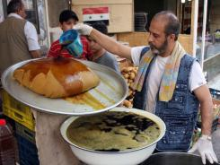 A man prepares a licorice drink on Monday, the first day of the Muslim holy month of Ramadan in downtown Damascus, Syria.