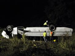 Rescue crews investigate an overturned tour bus alongside Interstate 81 in Whitney Point, NY,