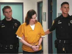 Sherrif's deputies escort Michele Kalina, 45, center, to her sentencing from central booking Thursday, Aug. 4 in Reading, Pa. Kalina was sentenced to 20 to 40 years in prison after pleading guilty to murder in connection with the deaths of five newborns.