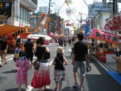A family walks along a street during the Tanabata festival in Iwaki city, Fukushima prefecture, Japan, Sunday.