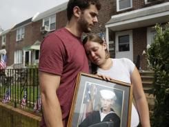 Charles Strange III and his sister, Katelyn, hold a photo of their brother, Petty Officer First Class Michael Strange, who was one of the Navy SEALs killed in a helicopter crash in eastern Afghanistan on Friday.