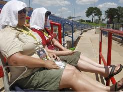 Fans keep cool at the Japan-Canada World Cup of Softball game in Oklahoma City, Thursday, July 21. Oklahoma racked up the country's highest average monthly temperature ever during July.