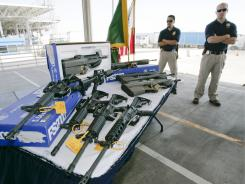 Customs and Border Protection officers stand by guns confiscated along the U.S.-Mexico border in 2009.