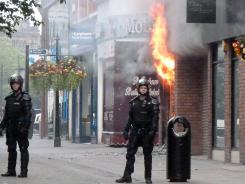 A store burns in Manchester on Tuesday after the third consecutive night of riots.