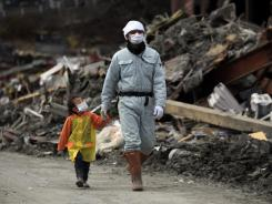 A man and his daughter walk in an area nearly a month after it was devastated in the March 11 tsunami.