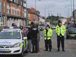 Police officers at the scene where three men were killed after being hit by a car in Birmingham.
