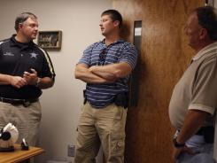 Warren County Sheriff Jackie Metheny, left, talks with investigators Kevin Murphy and Jody Cavanaugh, right, in McMinnville, Tenn.
