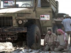 Libyan rebels pray near a multi-rocket launcher on the outskirts of Brega, in eastern Libya.