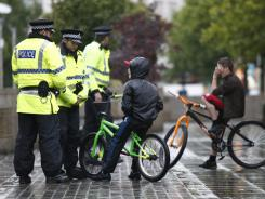 British police officers speak with children Wednesday after Tuesday night riots in Manchester, England.