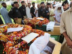 Pakistani police officers and others look at their colleagues and friends who lost their lives in a suicide bombing in Peshawar.